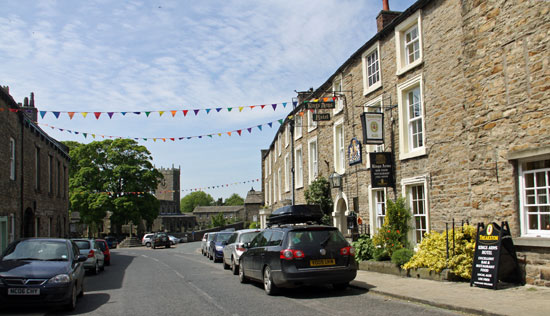 Askrigg with bunting out to welcome holidaymakers